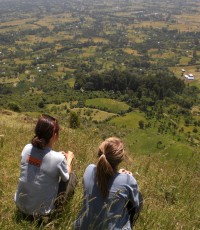 Sachi rests at the top of a hike with a fellow teacher, looking out over Yetebon.