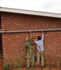 Stephen and his father look at fixing a pipe when his parents visited him at Nyumbani.
